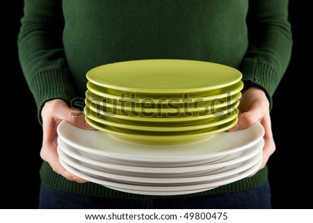 female hands holding a pile of green and white dishes - stock photo