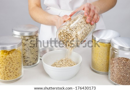 Female hands holding a pot with raw oatmeal, grey background - stock photo