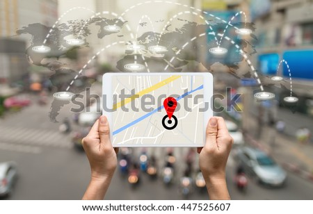 female hands holding a tablet showing part of navigator map on connection line over the world map with blurred photo of traffic jam, Navigation concept,Elements of this image furnished by NASA - stock photo