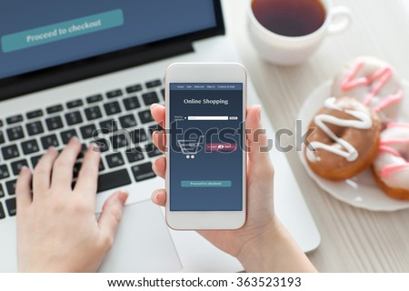 female hands holding a white phone with online shopping on the screen on a table with laptop - stock photo