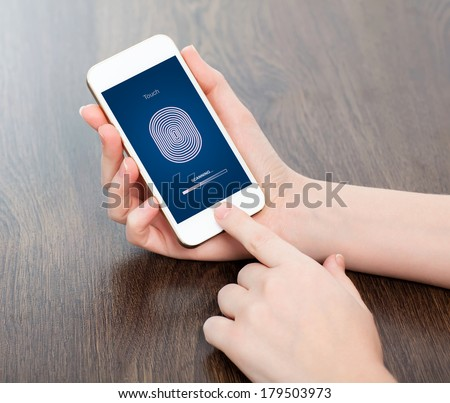 female hands holding a white touch phone and entering the PIN code of fingerprint  - stock photo