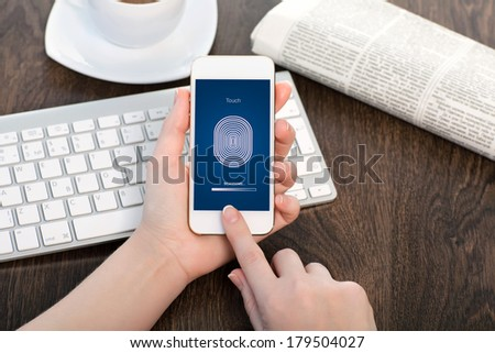 female hands holding a white touch phone over the desk in the office and entering the PIN code of fingerprint  - stock photo