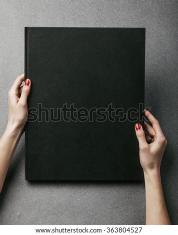 Female hands holding big black book. Vertical - stock photo