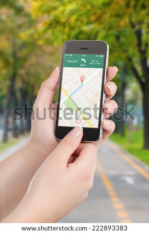 Female hands holding black mobile smart phone with map gps navigation application with planned route on the screen. Blurred street view on the background.  - stock photo