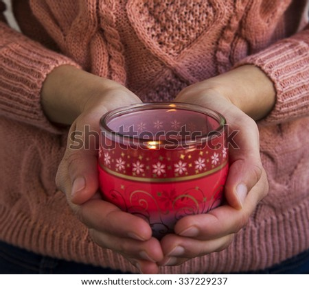 Female Hands Holding Christmas Scent Burning Candle - stock photo