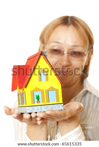 Female hands holding concept house. Selective focus on the house - stock photo