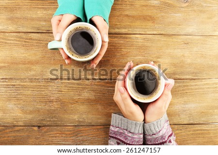 Female hands holding cups of coffee on rustic wooden table background - stock photo