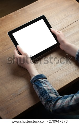female hands holding digital tablet computer with isolated screen over old grey wooden background table - stock photo
