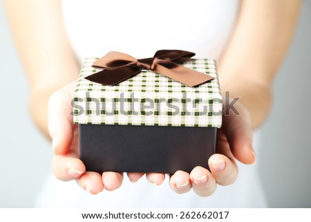 Female hands holding gift box - stock photo