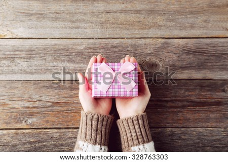 Female hands holding gift box on grey wooden background - stock photo