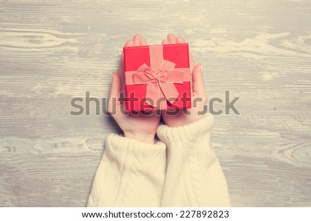 Female hands holding gift on wooden table. - stock photo