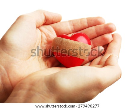 Female hands holding heart with plaster isolated on white - stock photo