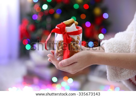 Female hands holding jar with Christmas cookies - stock photo