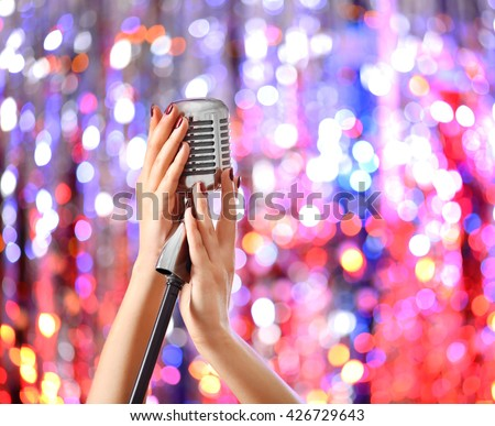 Female hands holding microphone against bright glitter background - stock photo
