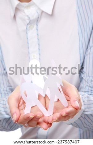 Female hands holding paper people, closeup, focus on the hands - stock photo
