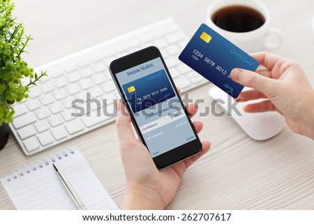 female hands holding phone with mobile wallet for online shopping over the desk  - stock photo