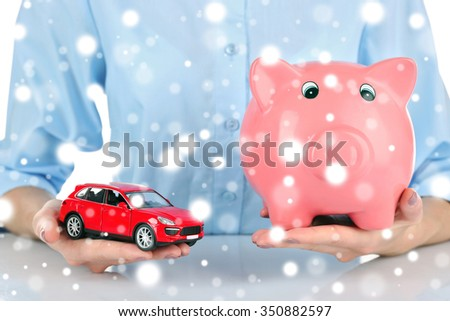 Female hands holding piggy bank and model of car over snow effect - stock photo
