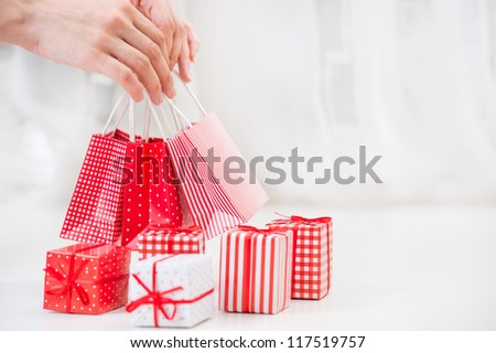 Female hands holding red gift bags near Gift boxes - shopping and holiday concept - stock photo