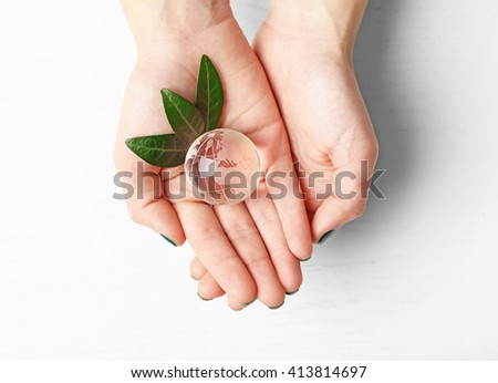 Female hands holding small glass globe over wooden table, top view - stock photo