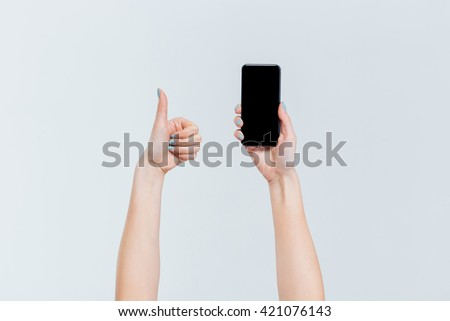 Female hands holding smartphone with blank screen and showing thumb up isolated on a white background - stock photo