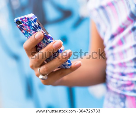 Female Hands holding smartphone. Young tanned  woman holding mobile phone,checking news and typing sms, wearing blue dress and ring.Mobile in bright cover. - stock photo