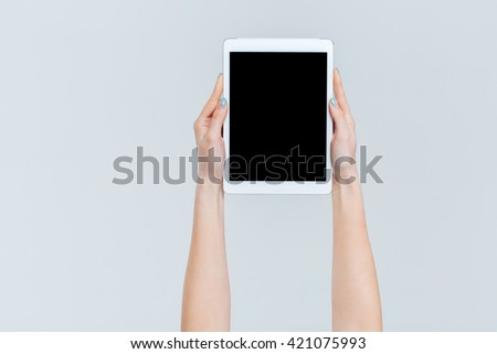Female hands holding tablet computer with blank screen isolated on a white background - stock photo