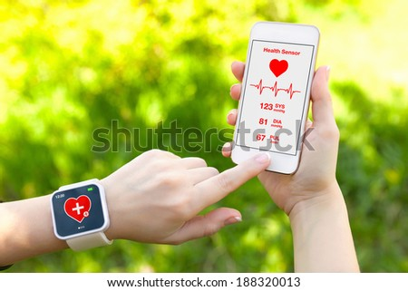 Female hands holding touch phone and smart watch with mobile app health sensor - stock photo
