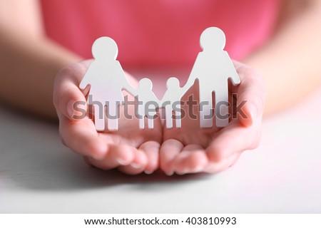 Female hands holding white family figures - stock photo