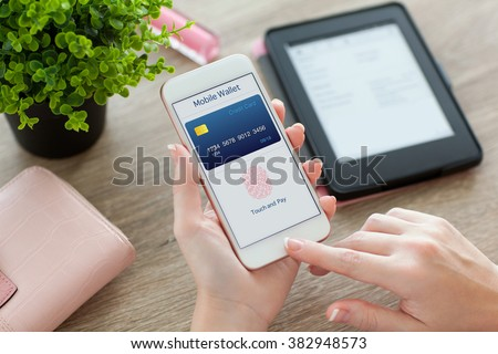 female hands holding white phone with app mobile wallet on the screen on the women table - stock photo