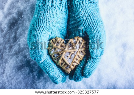 Female hands in light teal knitted mittens with entwined beige flaxen heart on a white snow winter background. Love and St. Valentines Day cozy concept. - stock photo