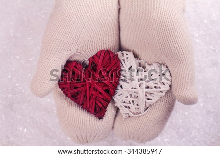 Female hands in white knitted cozy mittens holding two hearts   on a white snow background. Christmas tree decoration. Love concept. Winter and Christmas time - stock photo