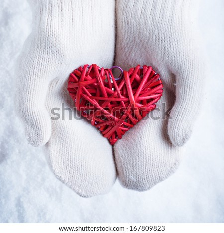 Female hands in white knitted mittens with a entwined vintage romantic red heart on a snow background. Love and St. Valentine concept. - stock photo