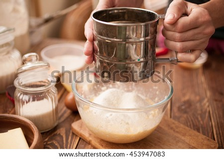 Female hands, ingredients and devices for preparation of cup-cakes on a wooden background. House pastries. Food concept. Flour, eggs, butter, mix for pastries.  - stock photo