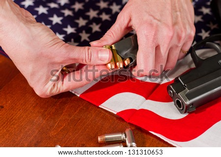female hands loading a hand gun with hallow point bullets and an american flag in the background - stock photo