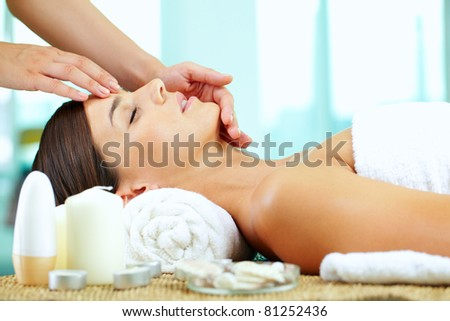 Female hands massaging young woman?s face - stock photo
