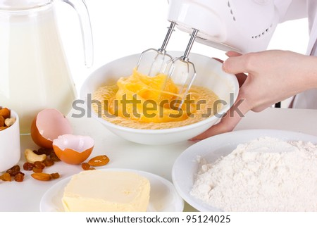 Female hands mixing eggs in bowl isolated on white - stock photo