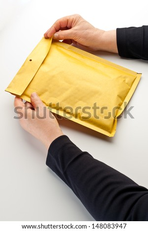 Female hands opening a small parcel/package in a yellow padded envelope. - stock photo