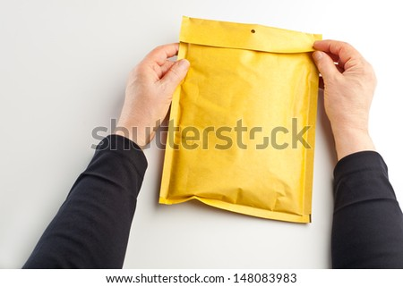 Female hands opening or closing a small parcel/package in a yellow padded envelope. - stock photo