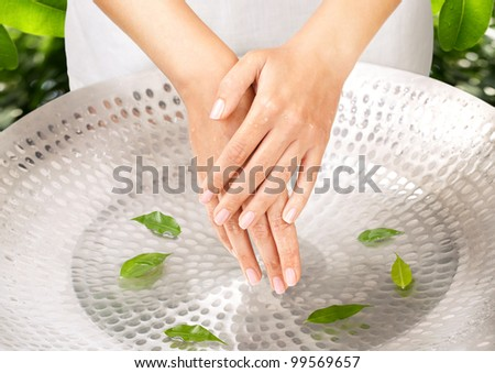 Female hands over sink with green leaves green background behind - stock photo
