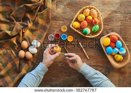 Female hands painting Easter eggs - stock photo