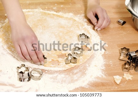 female hands pressing christmas molds in dough - stock photo
