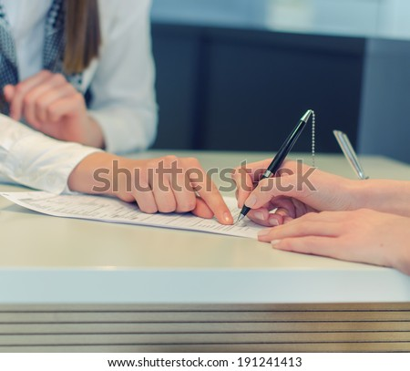 Female hands putting signature to agreement document in office - stock photo