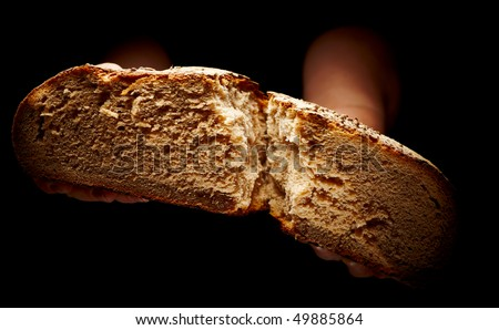 female hands sharing a brown loaf of bread isolated on black - stock photo