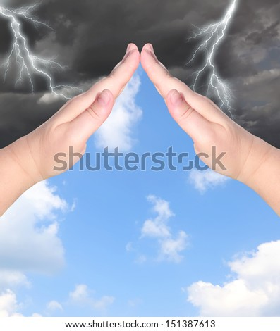 Female hands showing protection sign with the storm sky outside and blue sunny sky inside. Protection concept. - stock photo