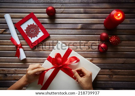 Female hands tying knot on giftbox and different Christmas symbols - stock photo