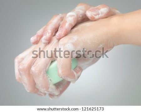 female hands washed with soap o grey gradient background - stock photo