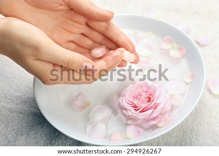 Female hands with bowl of aroma spa water on table, closeup - stock photo