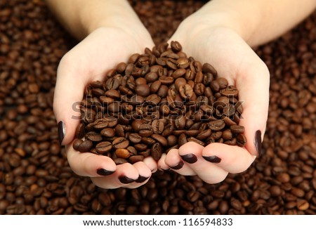 female hands with coffee beans, close up - stock photo