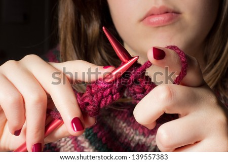 Female hands with knitting needles while knitting - stock photo
