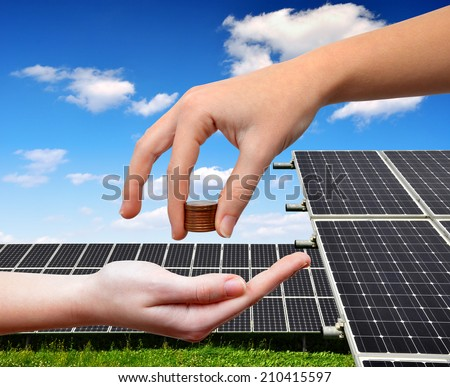 Female hands with money.In the background solar panel. - stock photo